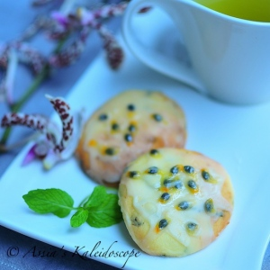 A stylized photo of passion fruit and goat cheese cookie with glaze on top on a plate
