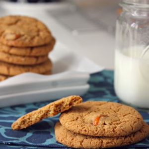 Thin kumquat gingersnap cookies on a plate with a glass of milk