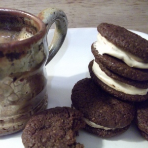 Hazelnut coffee sandwich cookies filled with marshmallow beside a cup of coffee