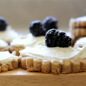 Side view of hazelnut shortbread topped with mascarpone and blackberries